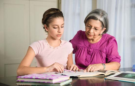 Hispanic grandmother helping granddaughter with homework